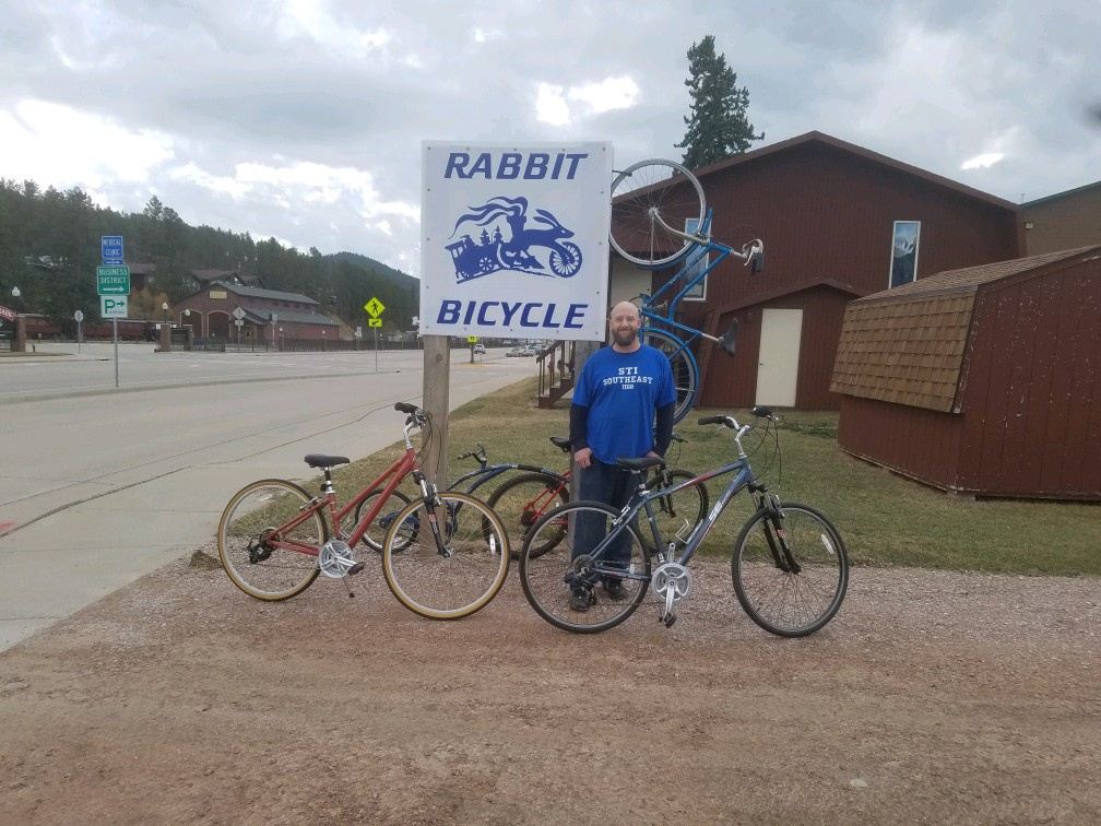 Brian standing in front of the Rabbit sign wearing a blue long-sleeved SouthEast Tech shirt.
