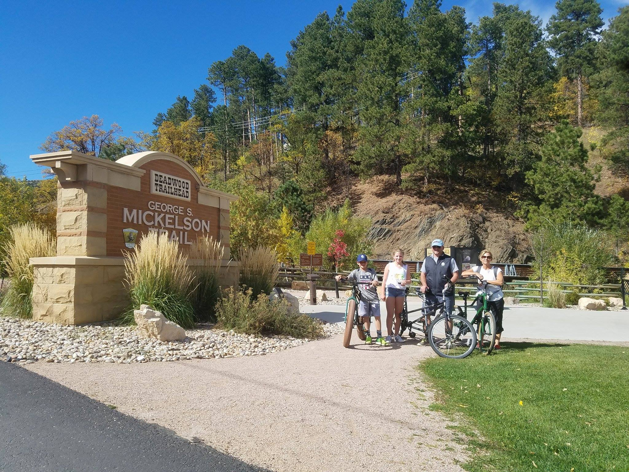 A group of bicyclists by the Mickelson Trail sign.