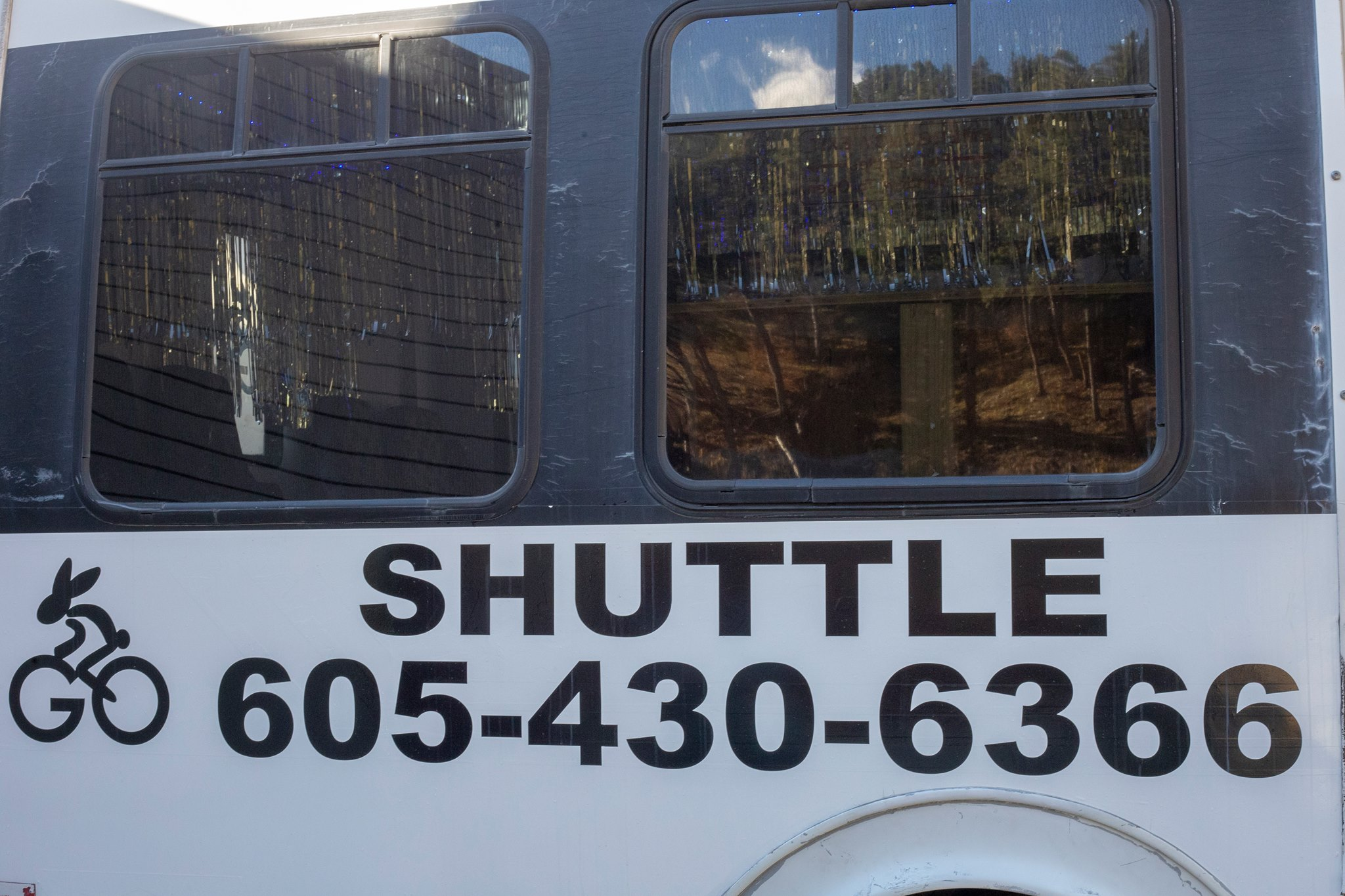 "One of the shuttles seen from the side. It has the Rabbit Bicycles logo on the far right, the word ""Shuttle"" written under the windows, and the phone number below that."