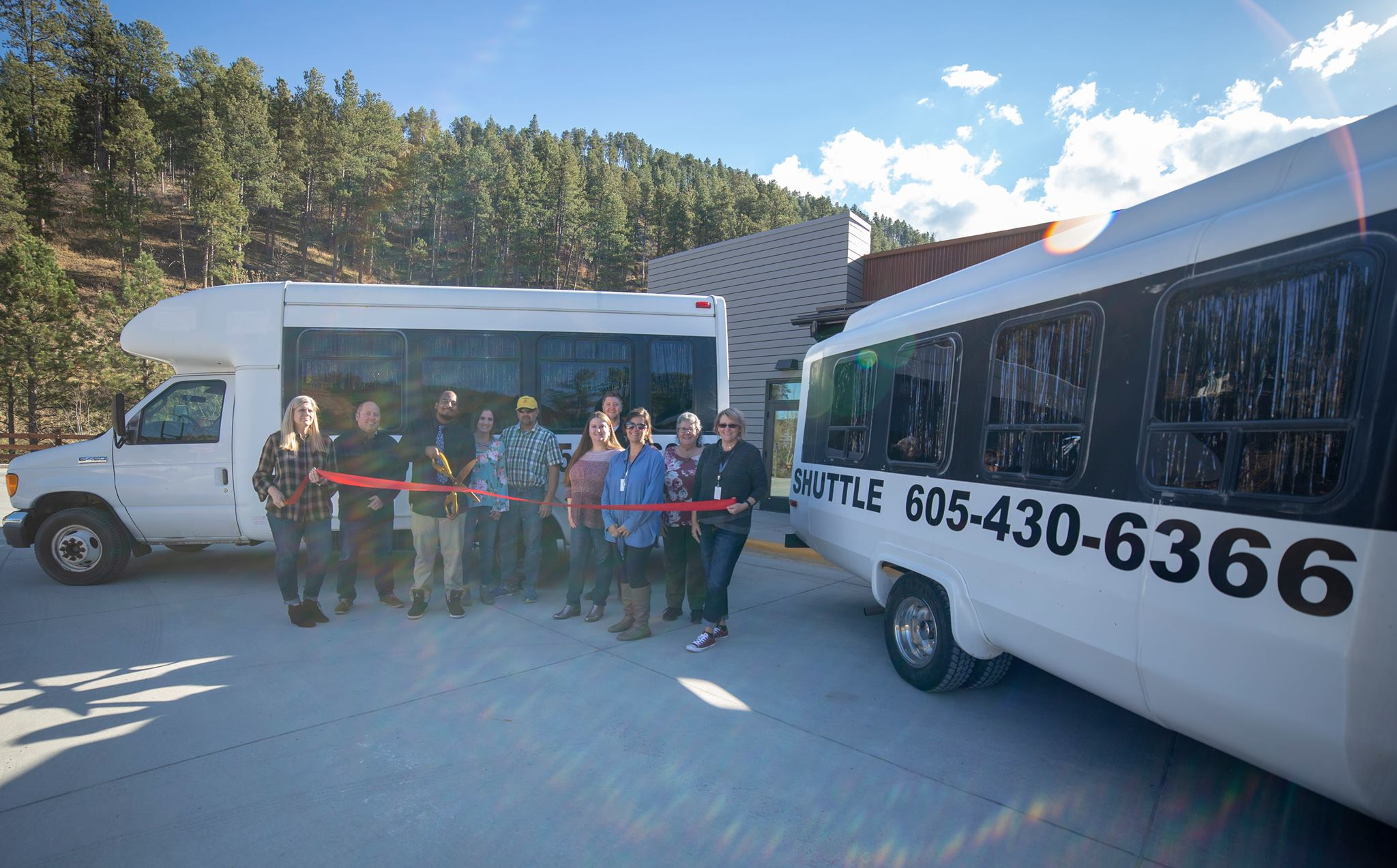 A group of ten people standing proudly in front of one of the shuttles during the ribbon cutting ceremony, including the driver - Jordan, and the owner - Stacey Phillips.