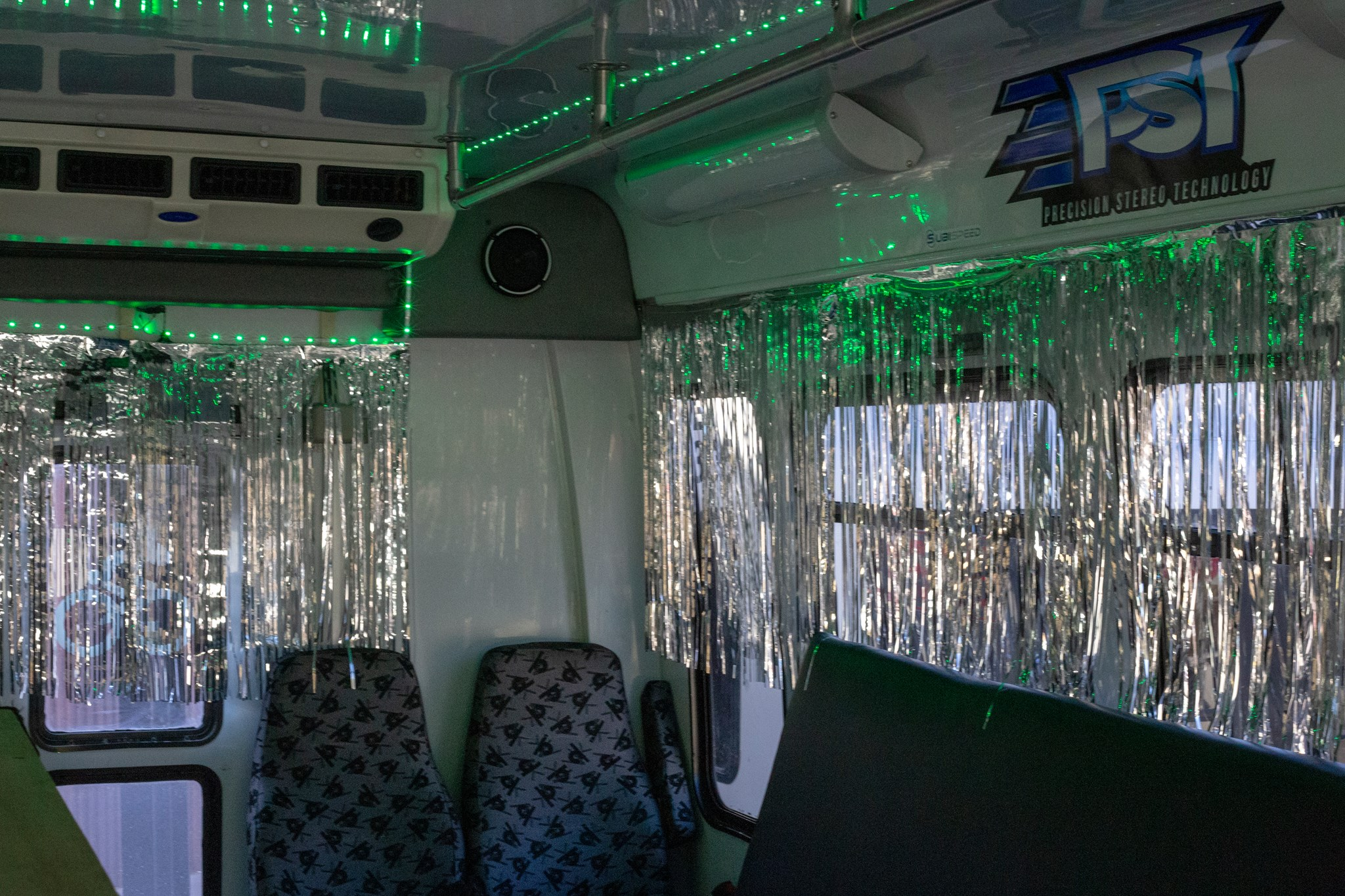 A picture of the interior of one of the busses. Green LED lights border the ceiling, glittering silver strands covering the windows, and comfortable-looking grey seats with black triangles.